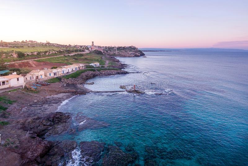 Sunset aerial view of the coastline of Portopalo and the Tafuri castle, Sicily, Italy royalty free stock photos