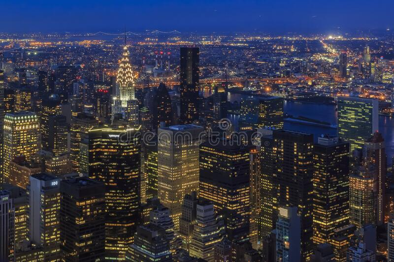 Sunset aerial view of iconic skyscrapers of New York Midtown Manhattan, and Long Island city skyline. With city lights stock photos