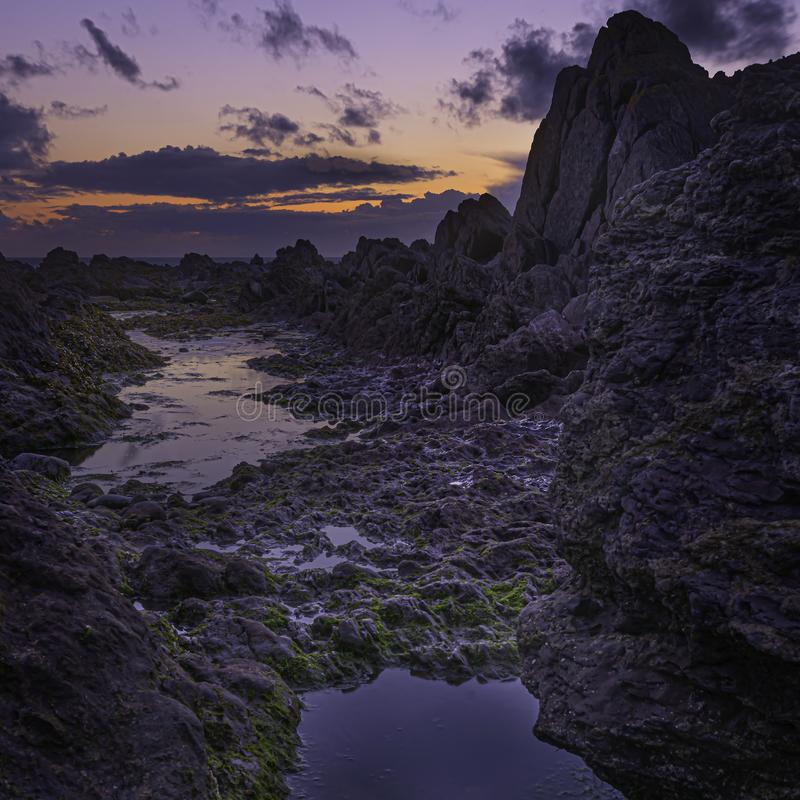 Sunset afterglow on magical rocky beach royalty free stock image