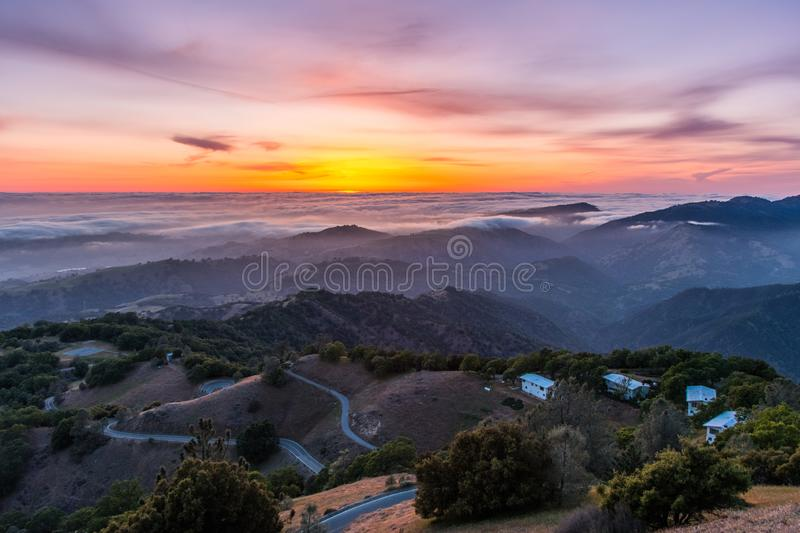 Sunset afterglow over a sea of clouds; winding road descending through rolling hills in the foreground; Mt Hamilton, San Jose,. South San Francisco bay area stock photo