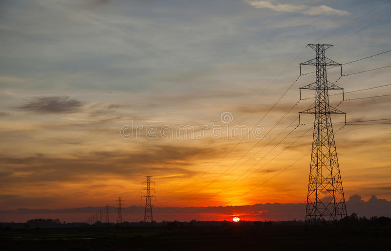 Sunset against high electric voltage pole stock photo