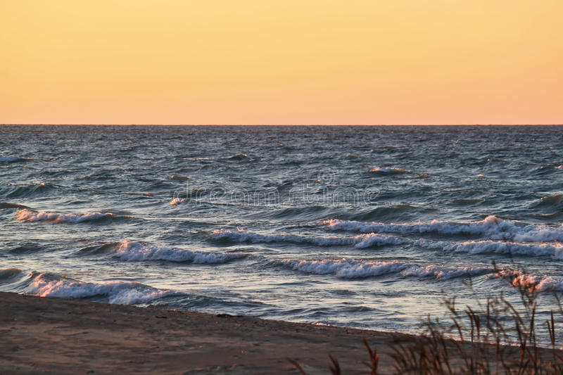 Sunset along beautiful Lake Michigan beach with view of Chicago skyline in far background. Orange sky Lake Michigan sunset is stunning as seen from a beach in royalty free stock photos