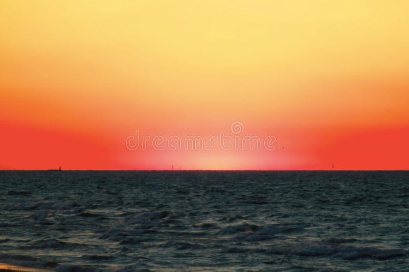 Sunset along beautiful Lake Michigan beach with view of Chicago skyline in far background. Orange sky Lake Michigan sunset is stunning as seen from a beach in stock image