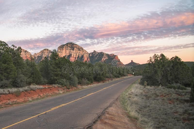 Sunset on highway with view of Sedona red rock formations in Arizona, USA. Sunset along two lane highway passing through red rock sandstone formations including stock image