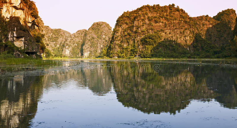 Sunset Along the Water. The limestone monoliths bathed in orange sunset light along the route to Tam Coc caves in Ninh Binh, Vietnam royalty free stock photo