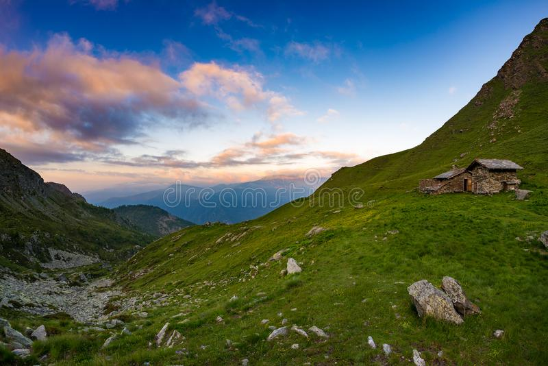 Sunset on the Alps, pasture and meadows with mountain hut refuge, colorful sky. Sunset on the Alps, pasture and meadows with mountain hut refuge, colorful sky royalty free stock photo