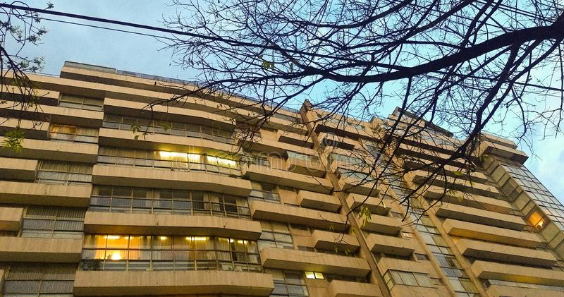 Sunset, apartment building. Last Days of winter. Building saying goodbye to daylight. Trees wanting to seize the scene; Creating uniformity royalty free stock images
