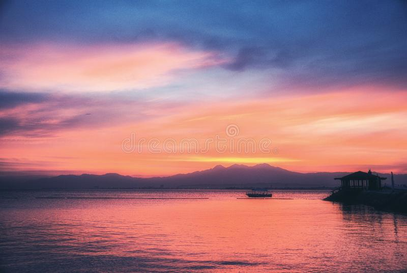 Sunset at Apo Mountain, Mindanao, Philippines. Sunset Mindanao, Philippines, With Mount Apo and Banca outrigger boat stock image