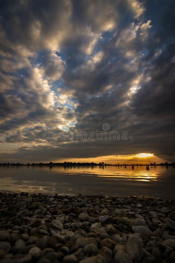 Sunset at the artificial reservoir Geeste, Germany. Frog perspective of the reservoir in Geeste, Germany. The sunset shines on the horizon. The clouds are stock image