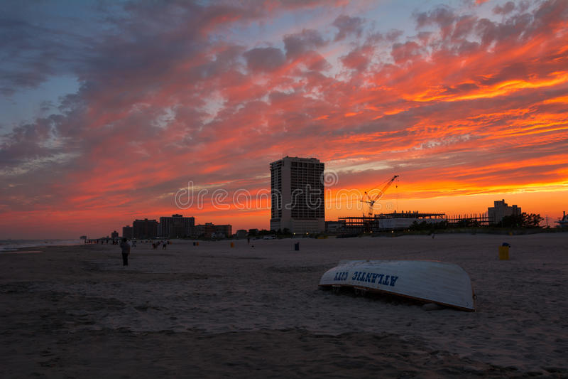 Sunset Atlantic City Beach. Brilliant pink clouds over Atlantic City beach at sunset, with life guard boat in the foreground royalty free stock images