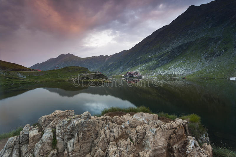 Sunset at Balea Lake. Lodge cabin on beautiful location. Lodge cabin at Balea Lake in Fagaras Mountain at the moment of sunset. Near Transfagarasan road stock image
