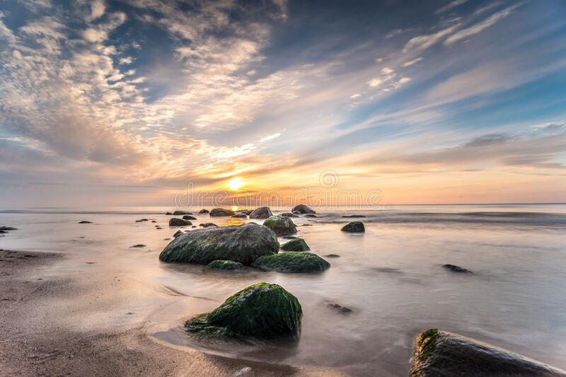 Sunset on the Baltic Sea. Sun between some Stones on a evening on the Baltic sea. Photography Long exposure. Palanga, Lithuania stock photography