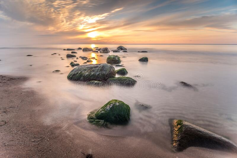 Sunset on the Baltic Sea. Sun between some Stones on a evening on the Baltic sea. Photography Long exposure. Palanga, Lithuania royalty free stock photos