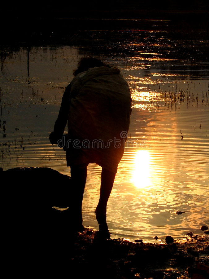 Sunset Banks. A poor woman washes clothes on the banks of an Indian river at sunset stock photos