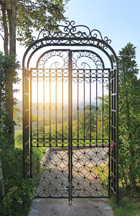 Sunset through the bars of wrought iron gate at hillside.  stock photos