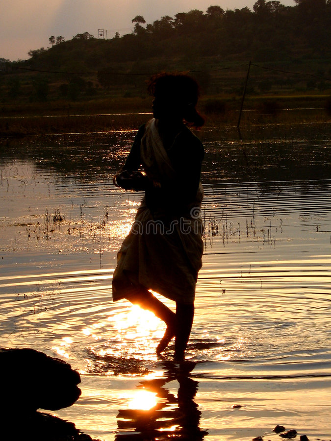 Sunset bath. A woman washes her clothes on the banks of an Indian river stock photos
