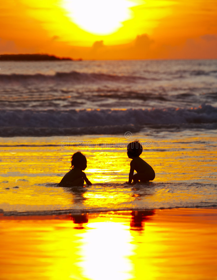 Sunset bath. View of two kids bathing during nice colorful sunset royalty free stock photos