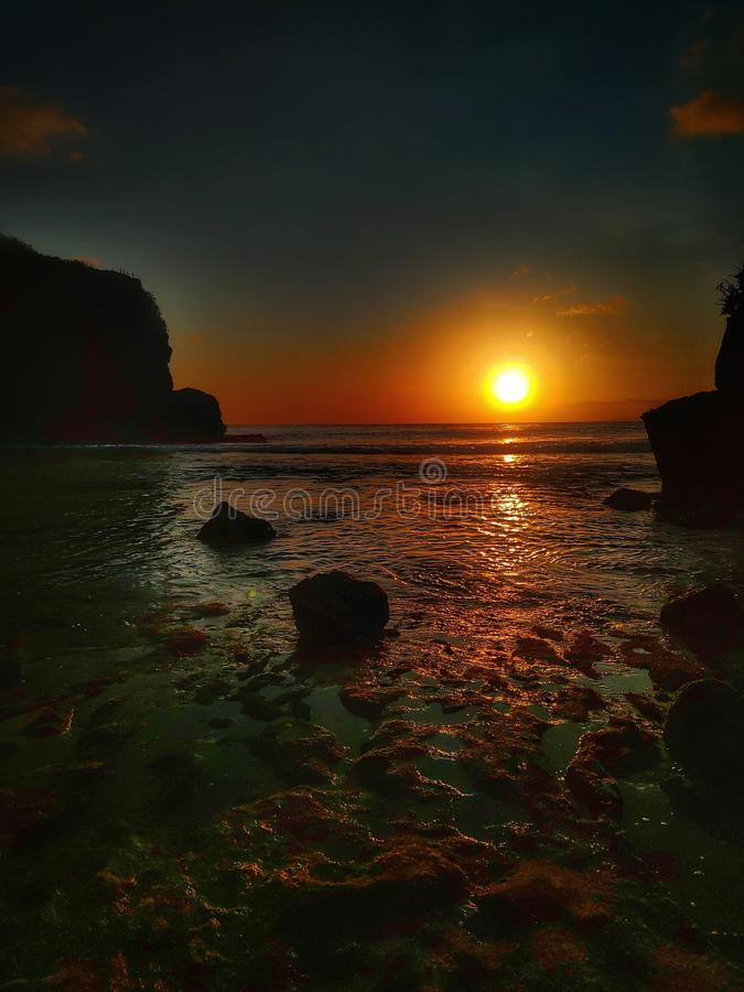 Sunset on batu bengkung beach malang indonesia. Ocean, wave, rock, reflection, nature, fullhd, android, wallpaper, sunrise, water, dawn, dusk, summer, autumn stock image