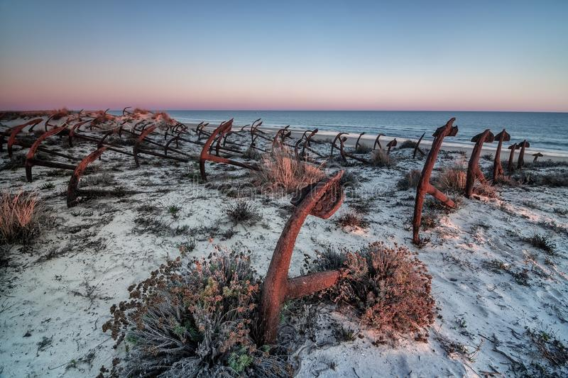 Sunset on the beach of Barril, cemetery of anchors. Tavira stock photography