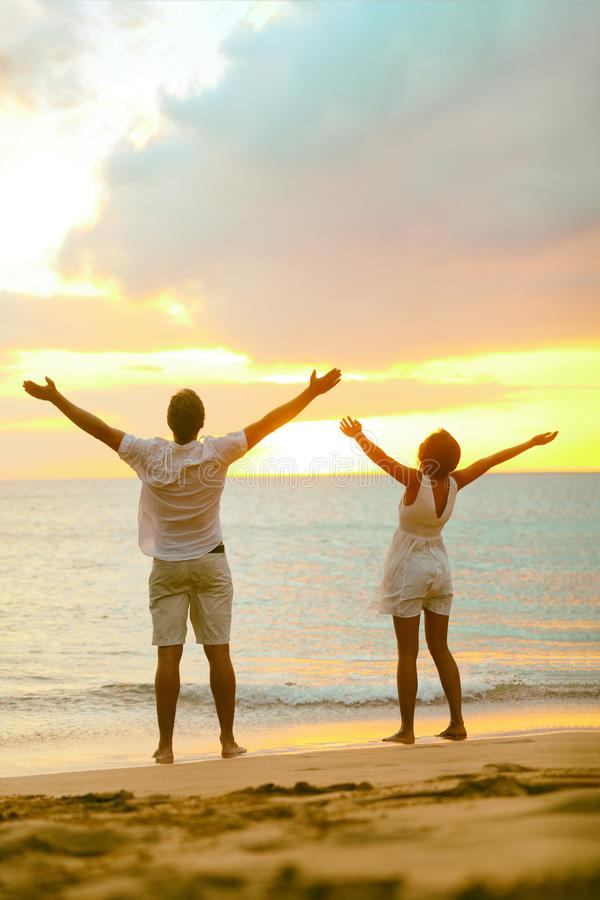 Sunset beach couple praising freedom with open arms up to the sky in success. Mindfulness, spirituality, faith, carefree people. Winning with raised hands stock image