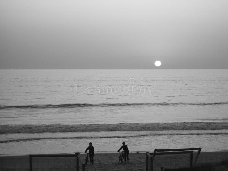 Sunset Beach Cyclists royalty free stock photos
