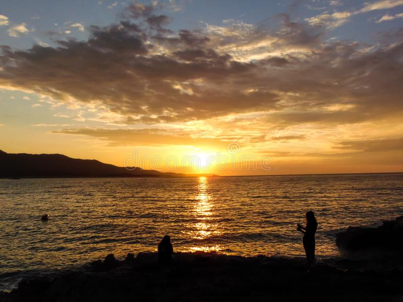 Sunset on the beach. Dusk on the shore of Ksamil, Albania. Blurred- image, shezlong, chaise, longue, water, sunset, beach, sky, sea, travel, ocean, landscape royalty free stock photography