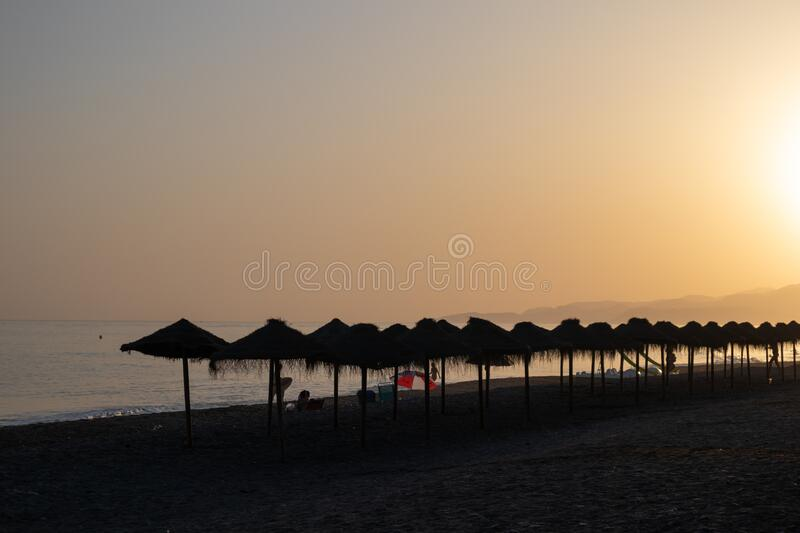 Sunset at the beach full of straw umbrellas in Salobreña, Granada, Spain. Last hours of sun at the beach full of straw umbrellas in Salobreña, Granada stock images