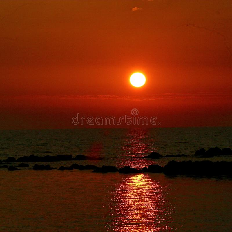 The sunset at the beach. This is the sunset at the beach in Marina di Massa in Italy stock image