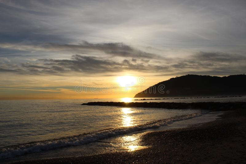 Sunset at the beach in Marinella di Sarzana. A beautiful cold afternoon in autumn at the beach in Italy. Looking at the sunset. The sun was slowly going down stock photo