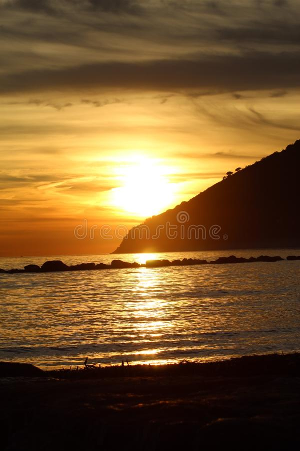 Sunset at the beach in Marinella di Sarzana. A beautiful cold afternoon in autumn at the beach in Italy. Looking at the sunset. The sun was slowly going down stock images
