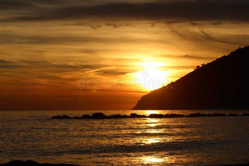 Sunset at the beach in Marinella di Sarzana. A beautiful cold afternoon in autumn at the beach in Italy. Looking at the sunset. The sun was slowly going down stock image