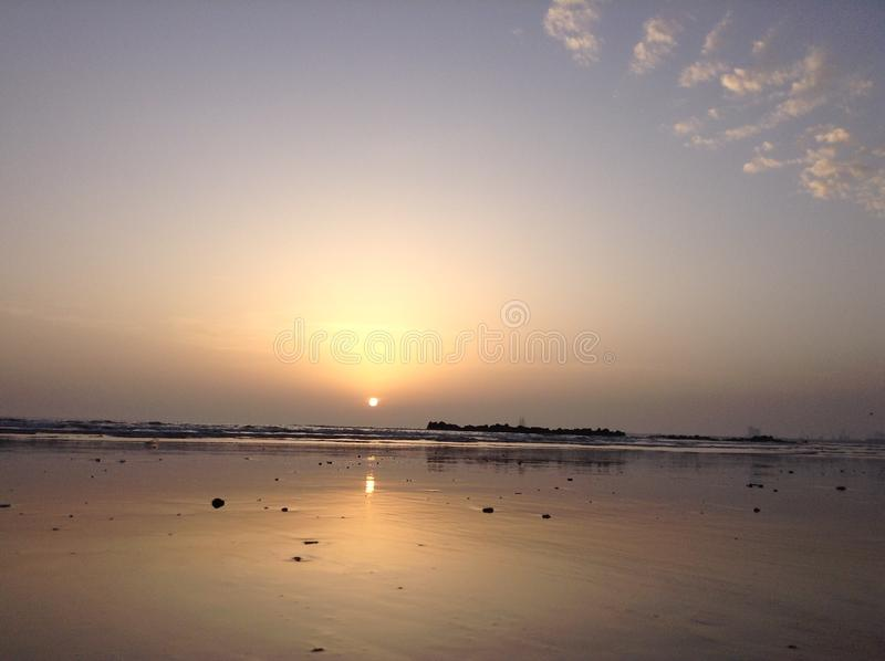 Sunset on the beach in Morocco Africa. Yellow sand. Blue sky. Ocean. Waves. Bright sun. Clouds in the sky. The sun is reflected in the water stock photos