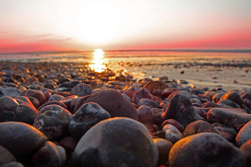 Sunset beach pebbles. Photo of a beautiful setting sun on the whitstable coast casting its pink twilight glow on the beach pebbles stock photos