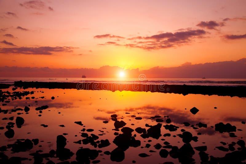 Sunset beach and rocks stock photography