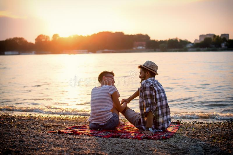 Sunset on beach, romantic scenery. On a river shore, young couple is having conversation royalty free stock photography