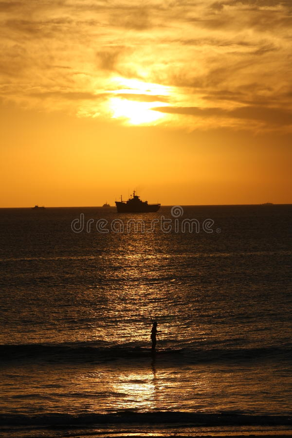 Sunset on the beach with a ship and surfer. stock photography