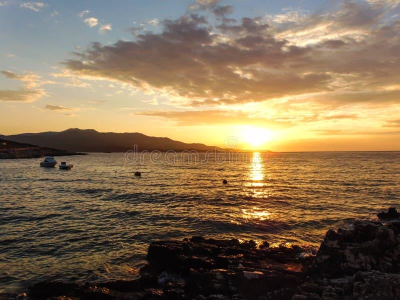 Sunset on the beach. Sunset on the shore of Ksamil, Albania. Blurred- image, water, beach, sky, sea, travel, lighthouse, ocean, landscape, coast, nature, blue stock photo