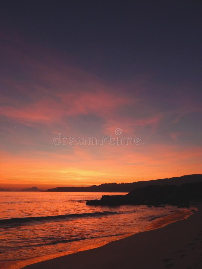 Sunset on the beach vertical. Sunset on the beach with the sun already low almost at night. Nerga, Spain stock image