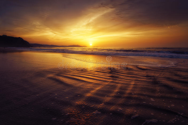 Sunset on beach with sun water reflections. Golden sunset on beach with sun water reflections stock photos