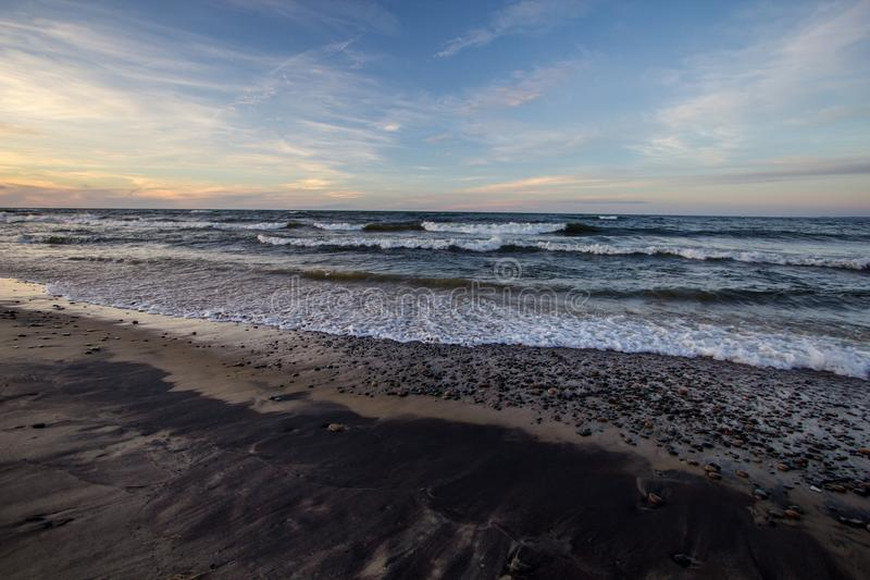 Sunset Beach With Waves On Lake Superior In Michigan. Wide sandy beach with waves crashing on the shore at Whitefish Point on the coast of Lake Superior. Wide royalty free stock photos
