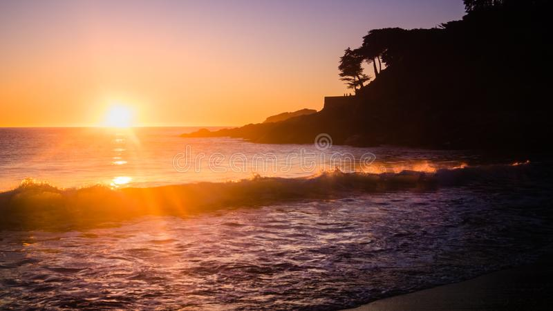 Sunset in the beach of Zapallar in Chile. Sunlight on waves and silhouettes of people in the back.  royalty free stock photography