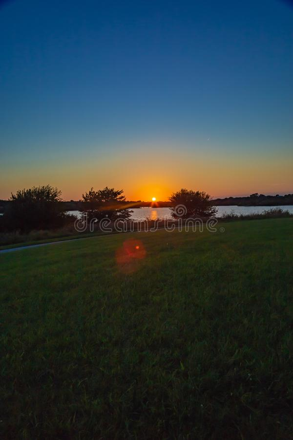Sunset with beautiful sky color over lake Zorinsky Omaha Nebraska. With the sun framed between two trees stock photography