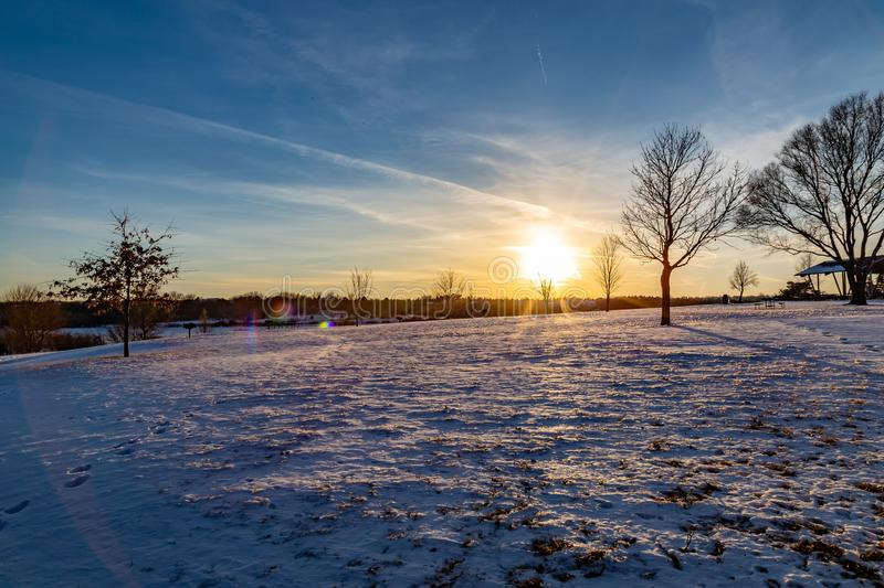Sunset with beautiful skyline over lake Zorinsky Omaha Nebraska. Beautiful skyline at dusk /sunset over lake Zorinsky in winter Omaha Nebraska USA. Snow on the royalty free stock photo