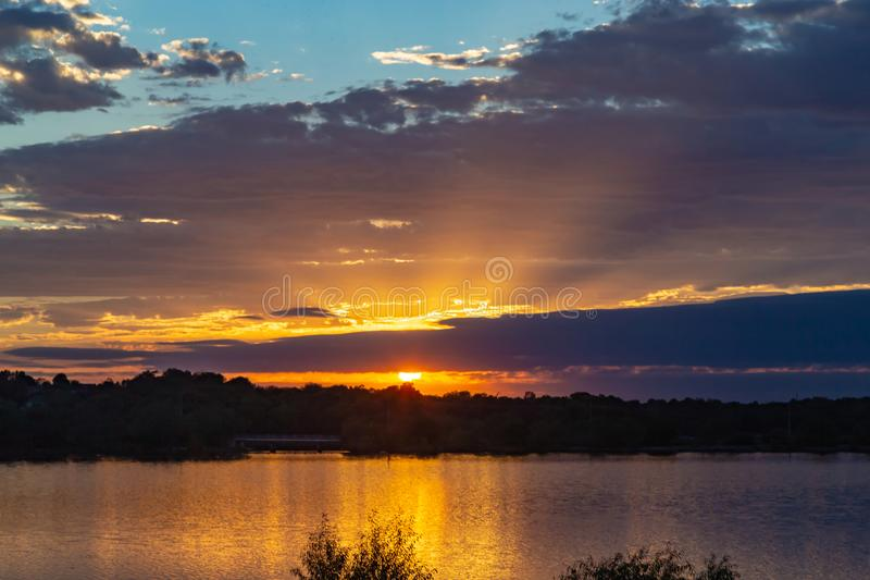 Sunset with beautiful skyline over lake Zorinsky Omaha Nebraska. Sunset with beautiful clouds in the sky and lake with golden sun reflection in the foreground royalty free stock photos
