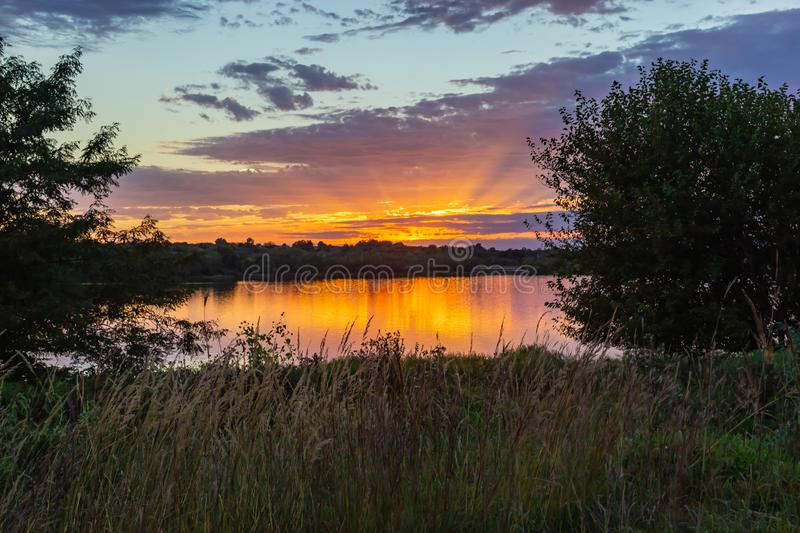 Sunset with beautiful skyline over lake Zorinsky Omaha Nebraska. Sunset with beautiful clouds in the sky and lake with golden sun reflection in the foreground stock image
