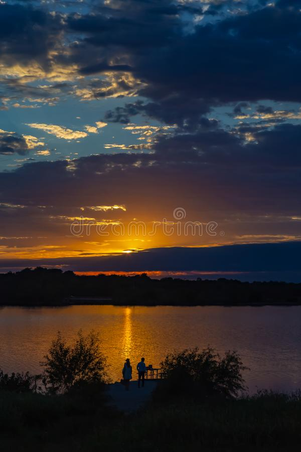 Sunset with beautiful skyline over lake Zorinsky Omaha Nebraska. Sunset with beautiful clouds in the sky and lake with golden sun reflection in the foreground royalty free stock image