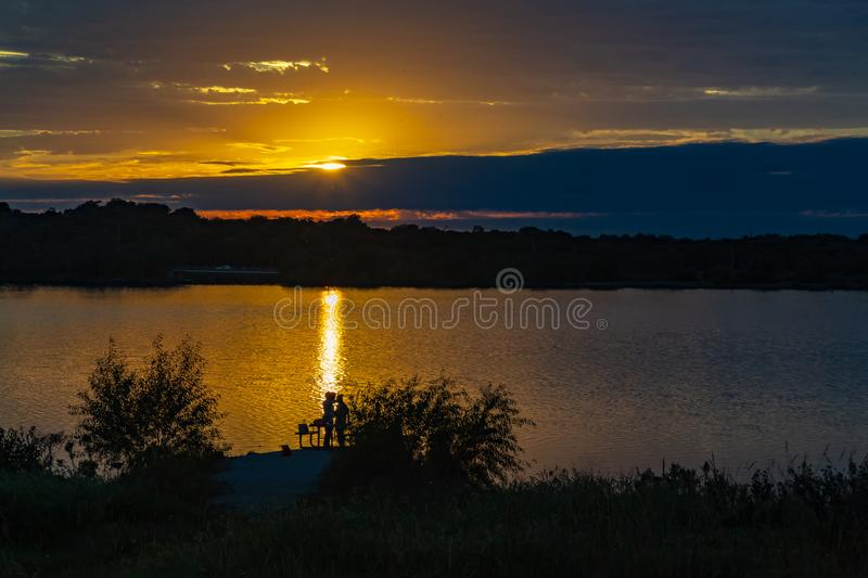 Sunset with beautiful skyline over lake Zorinsky Omaha Nebraska. Sunset with beautiful clouds in the sky and lake with golden sun reflection in the foreground royalty free stock images