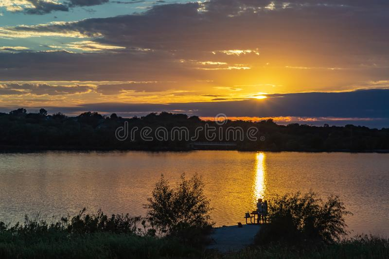 Sunset with beautiful skyline over lake Zorinsky Omaha Nebraska. Sunset with beautiful clouds in the sky and lake with golden sun reflection in the foreground stock images