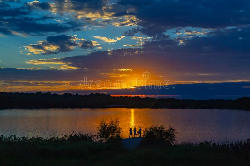 Sunset with beautiful skyline over lake Zorinsky Omaha Nebraska. Sunset with beautiful clouds in the sky and lake with golden sun reflection in the foreground royalty free stock photo