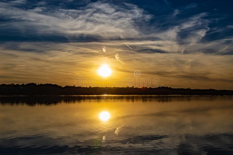 Sunset with beautiful skyline over lake Zorinsky Omaha Nebraska. There is reflection of the round sun outline and the surrounding vegetation in the lake stock images